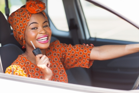 pretty african woman showing car key inside new vehicle