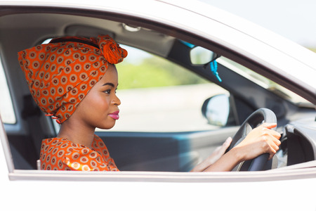 ethnic attire: beautiful young african woman driving a car