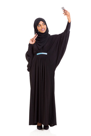 happy young muslim woman taking self portrait with smart phone photo