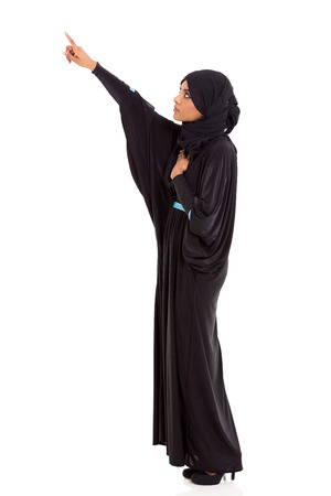 girl in dress: young arabic woman pointing empty copy space