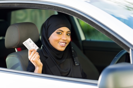 female driver: cheerful muslim woman showing a driving license she just got