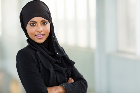 girl in dress: beautiful modern arabic office worker portrait with arms crossed Stock Photo