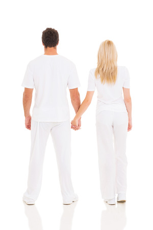 back view of young couple holding hands on white background photo