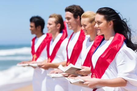 coro: feliz coro de la iglesia cantando en la playa Foto de archivo