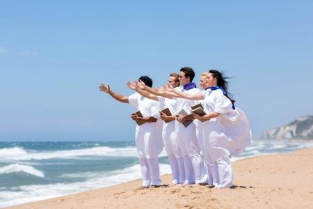 joven coro de la iglesia cantando en la playa Foto de archivo