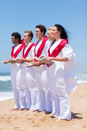 church group: group of young church choir singing on beach Stock Photo