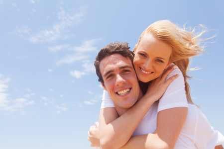 carrying girlfriend: portrait of young man carrying girlfriend on his back