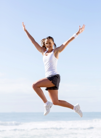 sportive: active young woman jumping outdoors