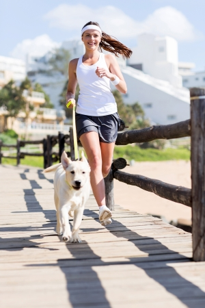 happy woman jogging with her dog photo