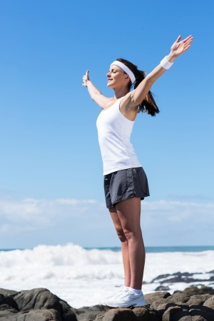 fitness young woman stretching arms up on beach