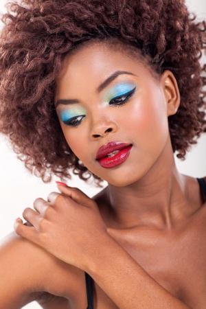makeup face: beauty portrait of african woman on plain background