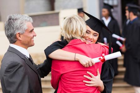 graduado femenino feliz abrazando a su madre después de la graduación