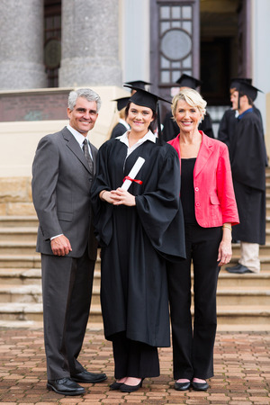 hogescholen: portret van een jong meisje afgestudeerde staan met ouders bij diploma-uitreiking Stockfoto
