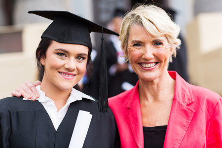 college graduate: beautiful young female graduate and mother at graduation ceremony