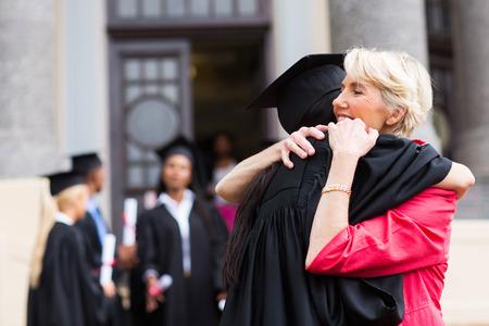 graduado de la hembra joven que abraza a su madre en la ceremonia de graduación
