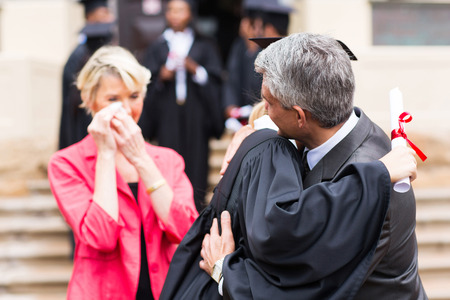 middle aged father hugging daughter at graduation ceremony