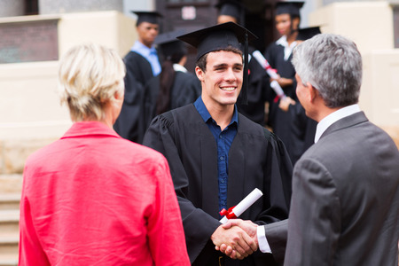 male graduate handshaking with his father at graduation photo