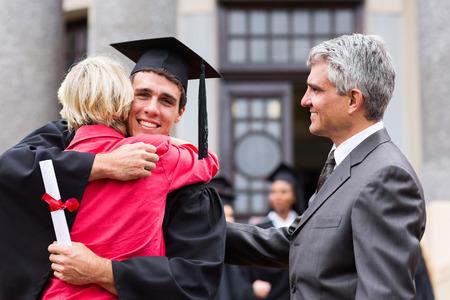 hogescholen: gelukkig mannelijke gediplomeerde knuffelen zijn moeder bij diploma-uitreiking Stockfoto