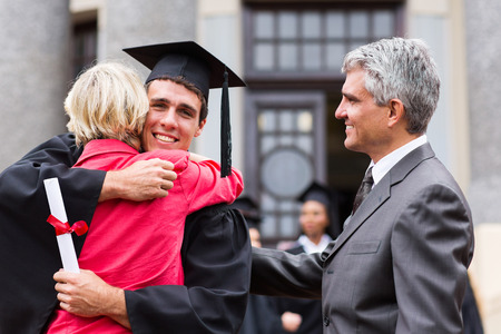 college graduate: happy male graduate hugging his mother at graduation ceremony