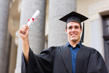 masters degree: happy male university student holding his graduation certificate