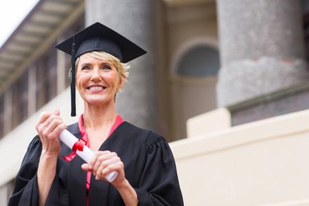 beautiful senior graduate holding certificate in front of university building