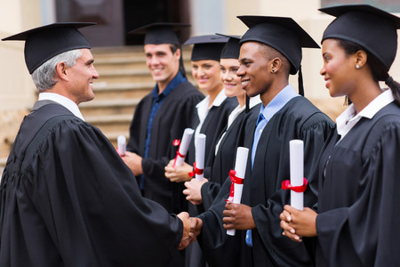 graduacion escolar: alto profesor universitario apret�n de manos con los j�venes titulados Foto de archivo