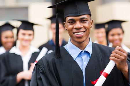gorros de graduacion: buena graduado afroamericano que mira macho delante de sus compañeros de clase