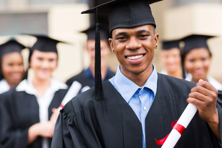 college graduation: good looking african american male graduate in front of classmates Stock Photo