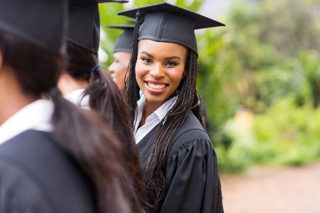graduado universitario muy africano mirando hacia atrás en la ceremonia de graduación
