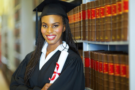 african student: beautiful african female graduate in library on graduation day Stock Photo
