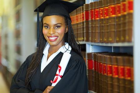 gorros de graduacion: graduado femenino africano hermoso en la biblioteca el d�a de graduaci�n Foto de archivo