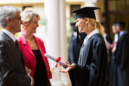 excited female graduate talking to parents on graduation day photo