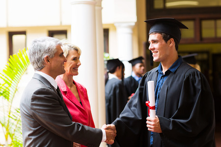 congratulating: proud father congratulating his son on graduation day