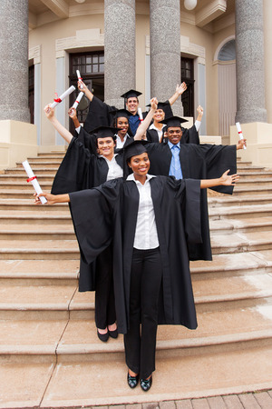excited graduates standing outside college building photo