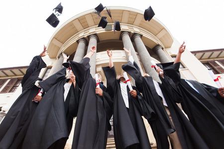 hogescholen: groep gelukkige afgestudeerden gooien afstuderen hoeden in de lucht viert Stockfoto