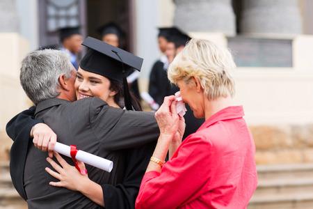 mooie jonge vrouwelijke afgestudeerde knuffelen haar vader aan het afstuderen Stockfoto