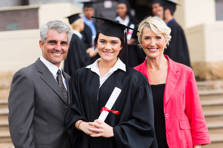 pretty young graduate with happy parents at graduation ceremony