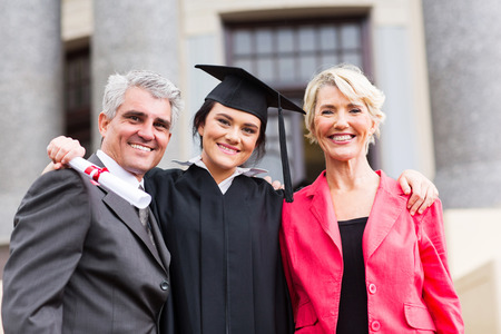 graduation caps: beautiful young female graduate with parents at ceremony Stock Photo