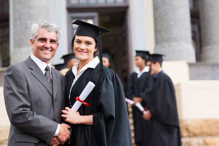 pretty female graduate with her father at university graduation photo