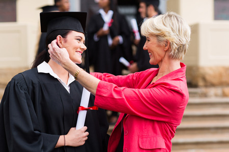 happy middle aged mother hugging her daughter at graduation ceremony photo