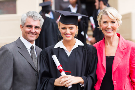 smiling young female graduate with parents at graduation ceremony photo