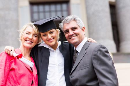 retrato de graduado universitario de sexo femenino feliz y los padres en la ceremonia