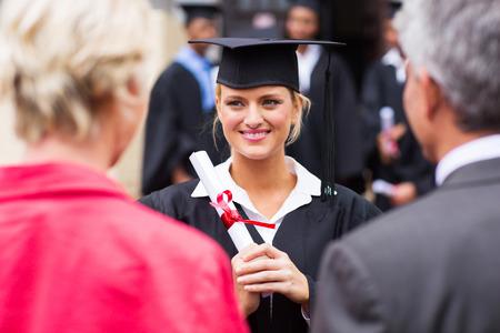 pareja de mediana edad de asistir a la ceremonia de graduación universitaria de su hija