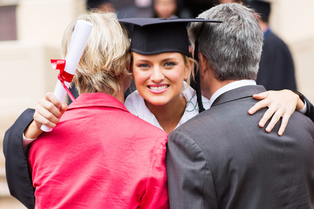gorgeous university female graduate hugging her parents after graduation photo