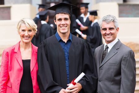 cheerful male college graduate and parents at graduation ceremony photo