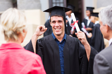 excited male graduate holding his diploma at graduation photo