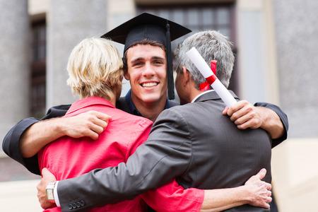 educacion universitaria: graduado hombre joven guapo, abrazando a sus padres en la graduaci�n