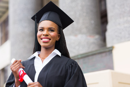 college graduation: pretty african american female graduate outside college building