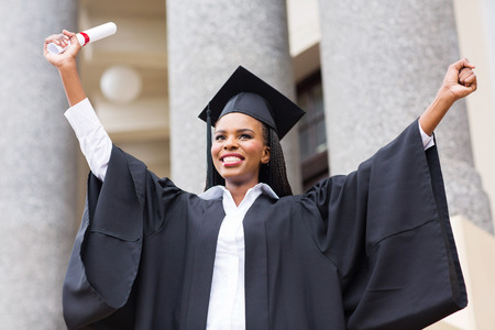 cheerful afro american female graduate standing in front of university building photo