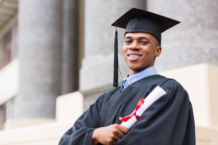 hogescholen: Portret van African American mannelijke gediplomeerde die buiten college Stockfoto